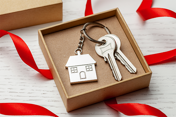 Why You Shouldn't Rule Out Home Buying This Holiday Season - Christmas box with red ribbon containing a silver house key chain and two keys.
